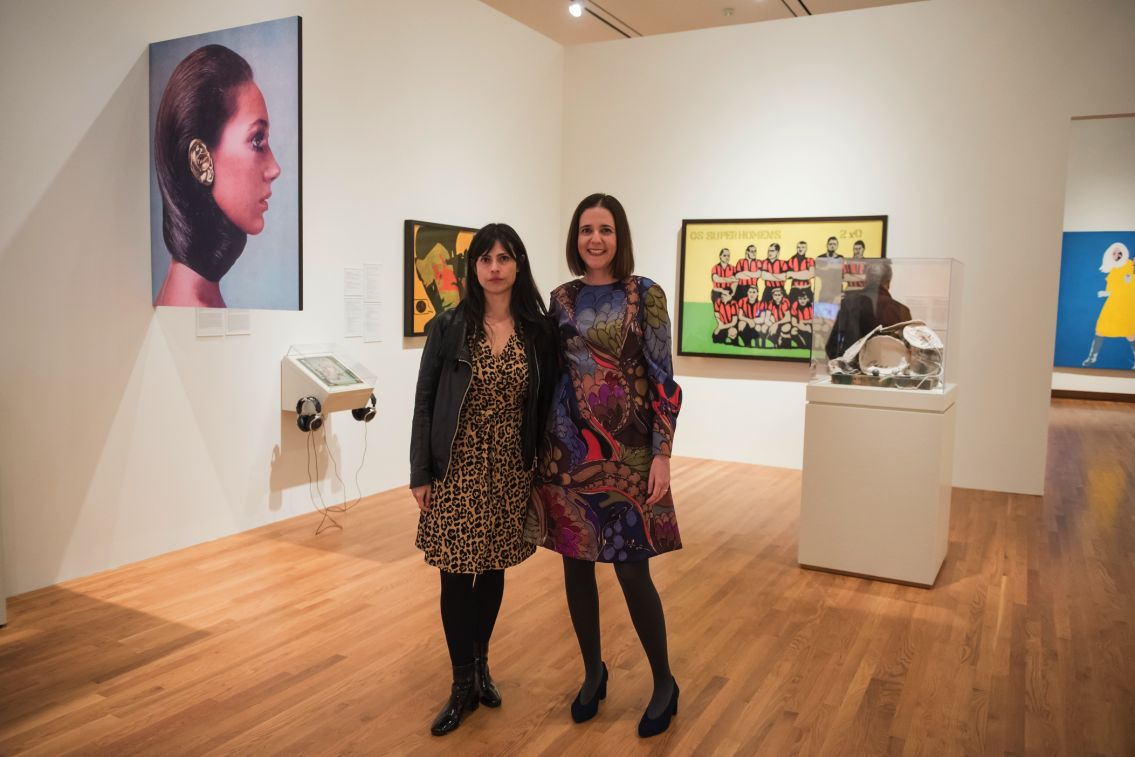 "Photo of ""Pop America"" art exhibit, with curator Prof. Esther Gabara and postdoctoral scholar Dr. Natalia de la Rosa, both in festive dresses, posing at gallery in front of several art works"