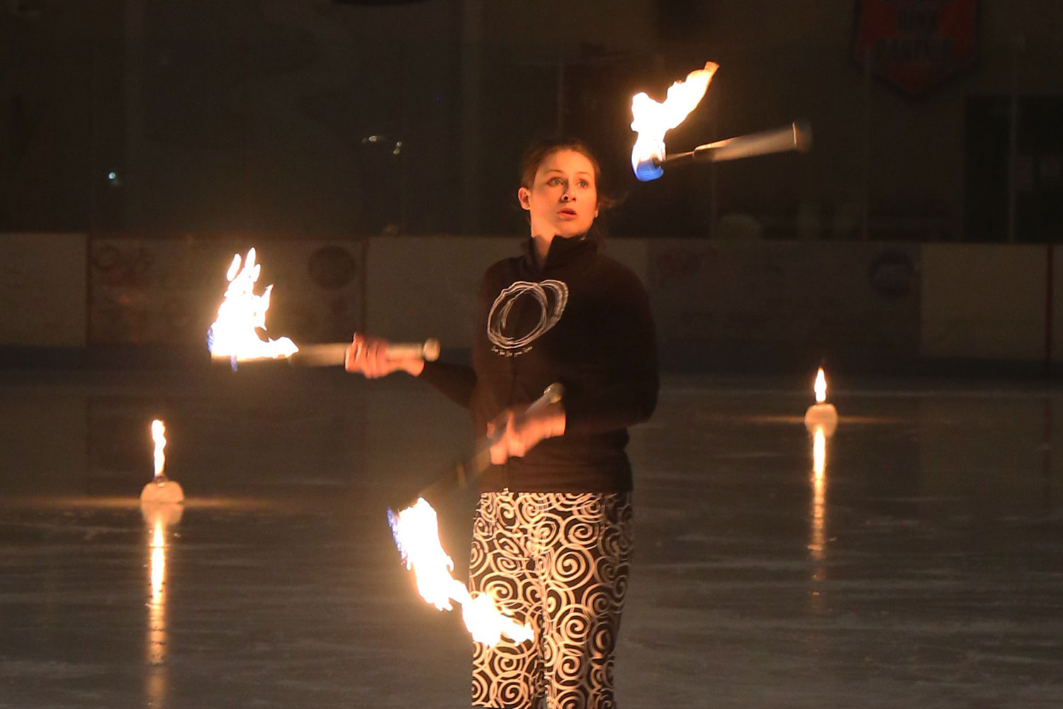 A woman juggling burning torches standing on an ice rink