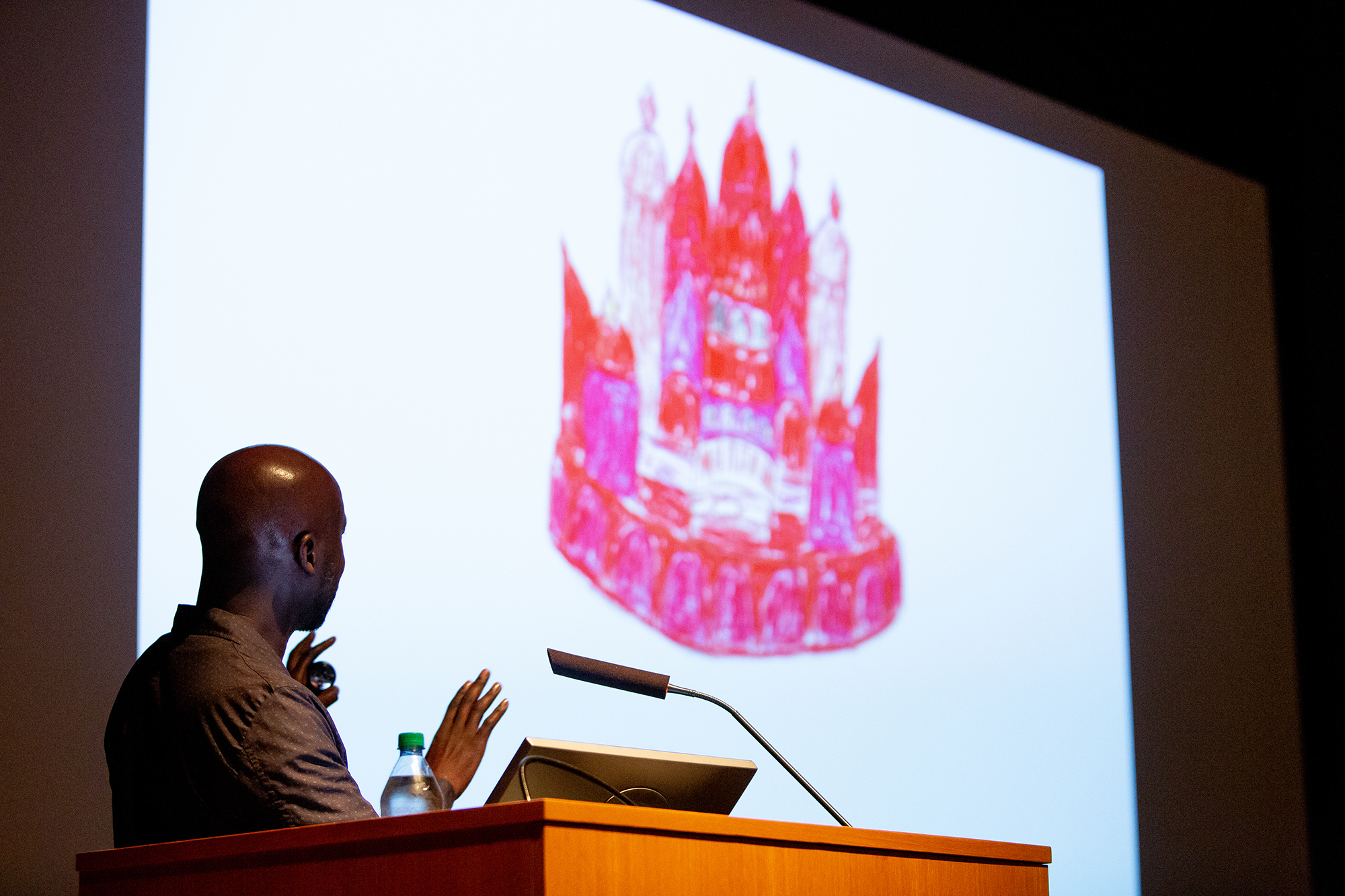 "David Adjaye in front of an illustration of a fantastical red palace - the inspiration for ""Ruby City."""