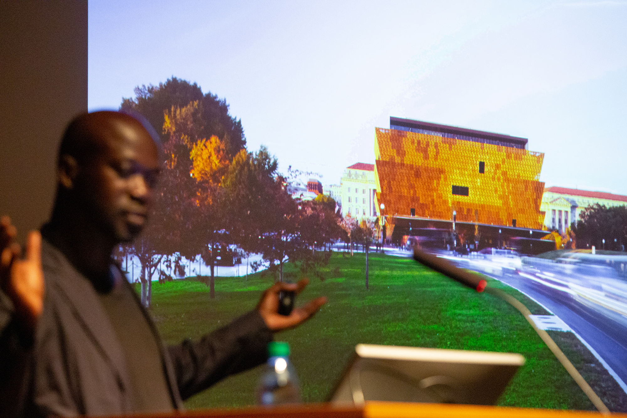 David Adjaye in front of a photo of the National Museum of African American History and Culture.