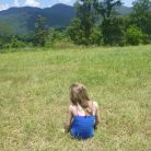 Young girl outside looking at mountains in the background