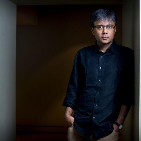 Amit Chaudhuri, standing in a doorway