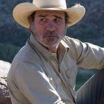Tommy Lee Jones in cowboy hat looking worried